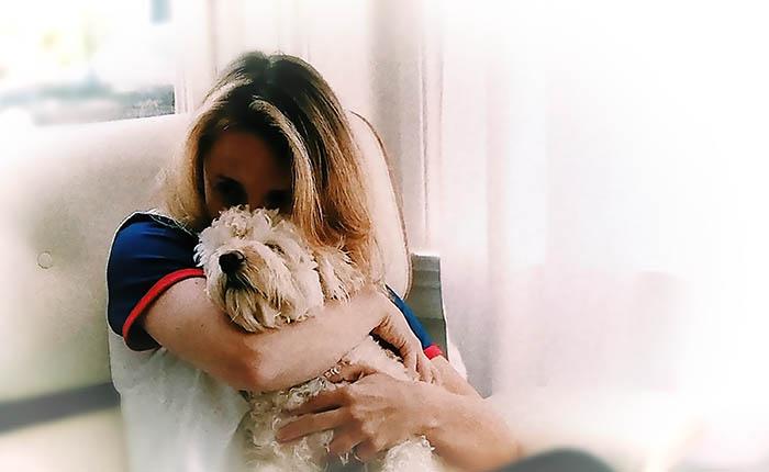 Vrouw met hond op de arm. Rouw verwerking komt na het afscheid nemen van je huisdier.